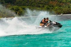Jonge kerels die pret in tropisch water op straalski hebben Stock Fotografie