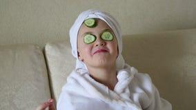 Jonge kinderen in de schoonheidssalon met komkommers op hun gezicht stock video