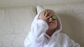 Jonge kinderen in de schoonheidssalon met komkommers op hun gezicht stock footage