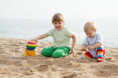 Jonge kinderen die op strand zitten Royalty-vrije Stock Afbeeldingen