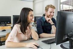 Jonge klasgenoten die een monitor en het bestuderen bekijken stock foto