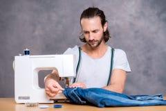Jonge kleermaker met naaimachine Stock Fotografie