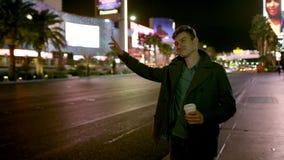 Jonge knap drinkt koffie op een straat bij nacht en probeert om een taxi te nemen stock footage