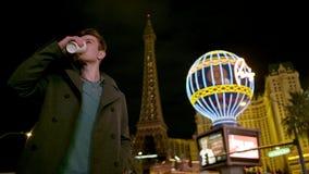 Jonge knap geniet van zijn heerlijke thee op een straat bij nacht stock videobeelden