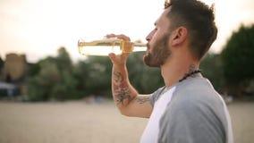 Jonge knap tatooed gebaard Kaukasisch mens het drinken bier van glasfles op het strand tijdens zonsondergang, steadycam schot stock video