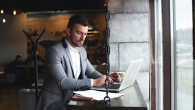 Jonge knappe aantrekkelijke gebaarde zakenmanzitting bij de lijst in een kostuum en het typen op laptop met mobiele dichtbijgeleg stock video