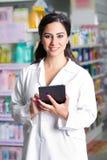 Jonge knappe apotheker met een tablet in een drogisterij Stock Afbeelding