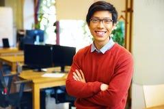 Jonge knappe Aziatische mens met gevouwen wapens stock afbeelding