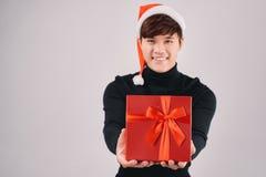 Jonge knappe Aziatische mens met santahoed die een rode gift geven royalty-vrije stock foto's