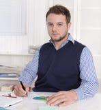 Jonge knappe boekhouder die met grafieken bij bureau werken. Stock Fotografie