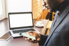 Jonge knappe donker-gevilde zakenman in een koffie die achter laptop met een kop thee werkt stock foto