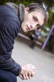 Jonge knappe droevige mensenplaatsing op bank in park Royalty-vrije Stock Foto's