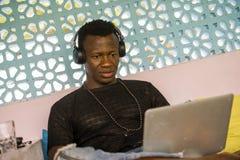 Jonge knappe en gelukkige hipster zwarte Afrikaanse Amerikaanse bedrijfsmens met laptop computer werken en hoofdtelefoons tevrede stock foto