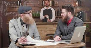 Jonge knappe gebaarde freelancers hebben een praatje op een informele commerciële vergadering stock videobeelden