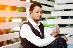 Jonge knappe gebaarde hipstermens die smartphone en het luisteren muziek met oortelefoons in de stad gebruiken Royalty-vrije Stock Fotografie