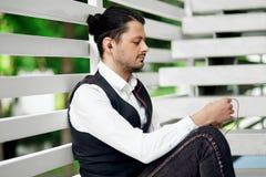 Jonge knappe gebaarde hipstermens die smartphone en het luisteren muziek met oortelefoons in de stad gebruiken Royalty-vrije Stock Foto