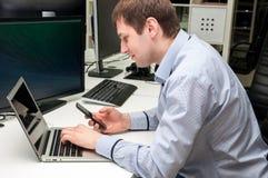 Jonge knappe gelukkige mens met computer in het bureau Stock Foto