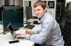 Jonge knappe gelukkige mens met computer in het bureau Programmin Royalty-vrije Stock Foto's