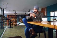 Jonge knappe hipsterkerel met baard het texting met zijn mobiele telefoon bij de bar en het hebben van een cappuccino stock foto