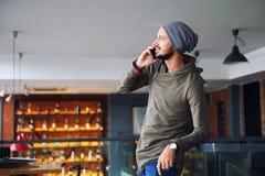 Jonge knappe hipstermens die smartphone in koffie gebruikt royalty-vrije stock afbeelding