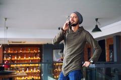Jonge knappe hipstermens die smartphone in koffie gebruikt stock afbeelding