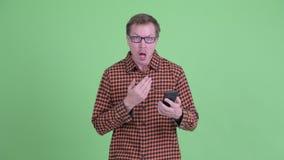 Jonge knappe hipstermens gebruikend telefoon en kijkend verrast stock video