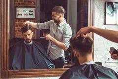Jonge knappe kapper die kapsel van de aantrekkelijke mens in herenkapper maken royalty-vrije stock afbeelding