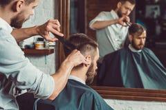 Jonge knappe kapper die kapsel van de aantrekkelijke mens in herenkapper maken royalty-vrije stock fotografie