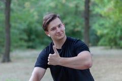 Jonge knappe Kaukasische mensenduimen omhoog bij het park stock afbeelding