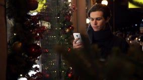 Jonge knappe kerel die smartphone op een bezige stadsstraat gebruiken in avond stock footage