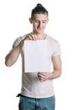 Jonge knappe kerel met een leeg blad die van document, omhoog glimlachend het blad bekijken Plaats voor handtekening, tekst Verti Royalty-vrije Stock Foto's