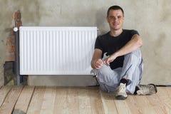 Jonge knappe loodgieterzitting op vloer met moersleutel in hand dichtbijgelegen Royalty-vrije Stock Foto's