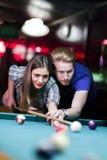 Jonge knappe man en vrouw die terwijl het spelen van snooker flirten royalty-vrije stock foto's