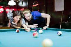 Jonge knappe man en vrouw die terwijl het spelen van snooker flirten stock fotografie