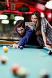 Jonge knappe man en vrouw die terwijl het spelen van snooker flirten royalty-vrije stock fotografie