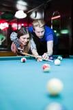 Jonge knappe man en vrouw die terwijl het spelen van snooker flirten stock afbeelding