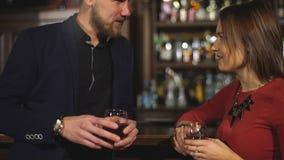 Jonge knappe man flirts met een vrouw bij een bar stock videobeelden