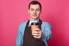 Jonge knappe mannelijke die barista stelt u voor kop van koffie door hem, gekleed elegant blauw overhemd, witte vlinderdas en bru royalty-vrije stock foto's