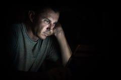 Jonge knappe mens bij laptop computer met lichte bezinning Royalty-vrije Stock Afbeeldingen