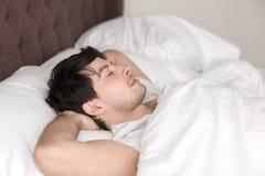 Jonge knappe mens die alleen in bed met gesloten ogen rusten Stock Foto