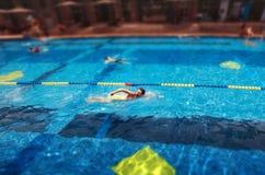 Jonge knappe mens die in de pool zwemmen stock foto