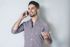 Jonge knappe mens die door celtelefoon spreken Royalty-vrije Stock Afbeeldingen