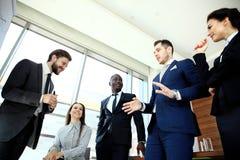 Jonge knappe mens die en iets gesturing bespreken terwijl zijn medewerkers die aan hem op het kantoor luisteren stock foto