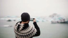 Jonge knappe mens die foto's van gletsjers neemt bij Ijslagune op smartphone Mannetje die in alleen IJsland reizen stock video