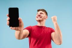 Jonge knappe mens die die het smartphonescherm tonen op blauwe achtergrond in schok met een verrassingsgezicht wordt geïsoleerd stock foto