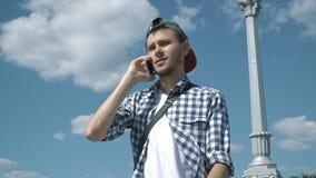 Jonge knappe mens die op de telefoon spreken stock footage