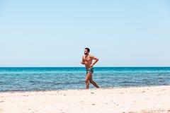 Jonge knappe mens die op het strand lopen stock foto's
