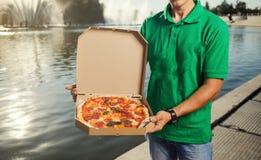 Jonge knappe mens die pizza leveren aan een klant stock afbeeldingen