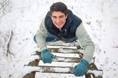 Jonge knappe mens die upwards houten ladder beklimt Stock Afbeeldingen