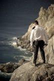 Jonge knappe mens die zich op rotsen bevinden die oceaan overzien Royalty-vrije Stock Foto